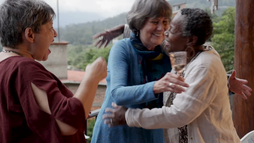 Beautiful African American senior woman in her 60s hugging her friends at a small party overlooking a spectacular mountain view in slow motion
