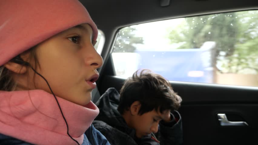 4k, slow motion. brother and sister twins, ride in the back seat of the car and listen to music in the headphones.   Shutterstock HD Video #33371854