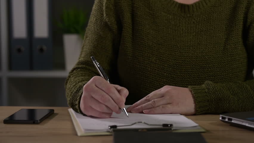 Female freelancer working overtime in home office, doing paperwork and accounting, writing notes and calculating budget | Shutterstock HD Video #33429181