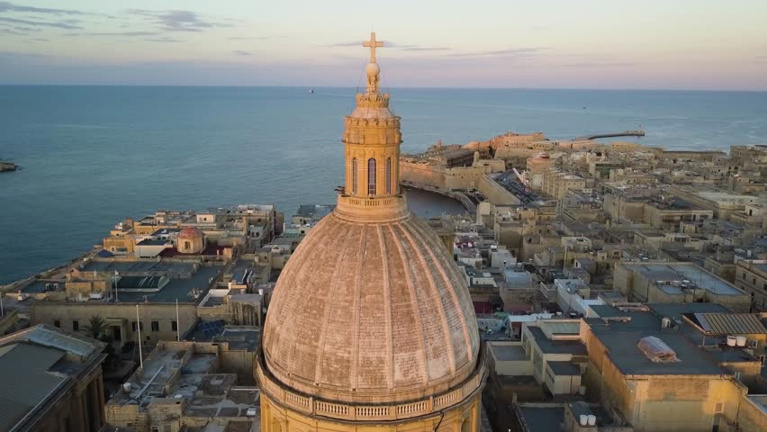 4k drone - Basilica Of Our Lady Mount Carmel at sunset. Ancient medieval city of Valletta, Malta. Island nation of Europe in the Mediterranean Sea.