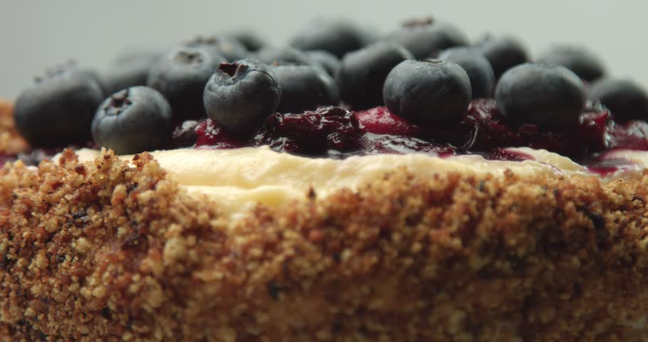 Close up of rotating homemade professional quality vanilla cake with fruit berries compote and fresh blueberries