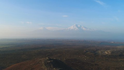 Aerovideo: area of beauty world at sunny morning. Unmanned aircraft flight over the Armenian snowy mount Ararat in Yerevan. Clear sky and sunshine showing all idyllic of picture, no people around