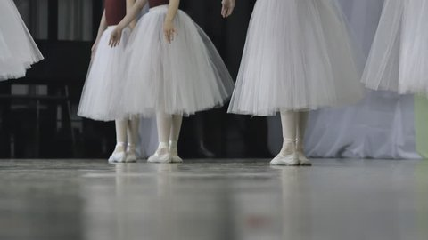 Ballet.Close-up of a girl's legs in white ballet shoes during ballet training. Element of classical dance. 4K