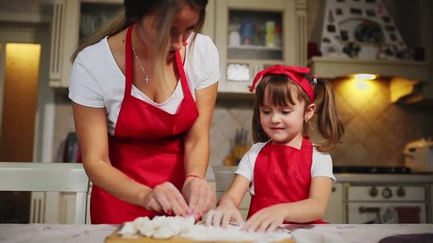Happy family in the kitchen mom and daughter in the kitchen playing with flour to have fun and mold the patties in the kitchen in the same red aprons. stedicam