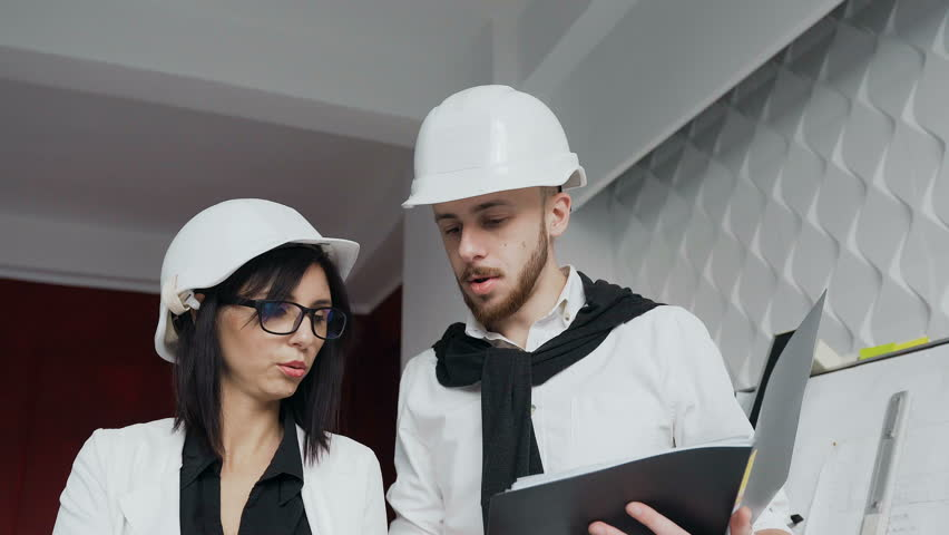 The development group of a project standing and discussing the two young architects working in helmets on a construction site a woman is an architect malvernweather Choice Image