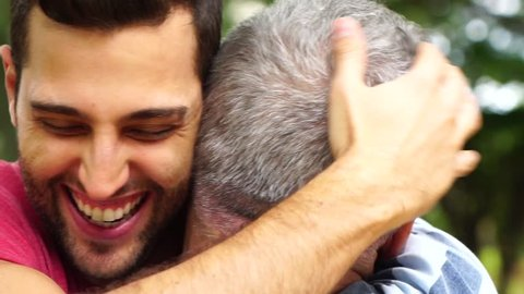 Adult son hugging his senior dad