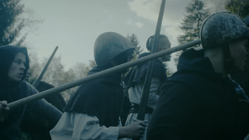 Large-Scale Medieval Battle Reenactment. Violent Tribe of Warriors Attack Wooden Fortress Wall, They Climb Ladders, Guards Try to Defend Fortification. Shot on RED EPIC-W 8K Helium Cinema Camera.