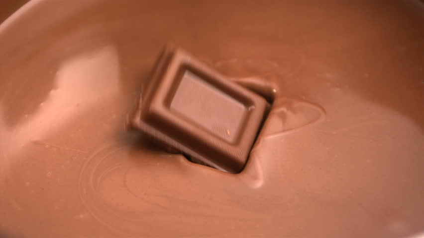 Square of chocolate falling into melted chocolate in slow motion