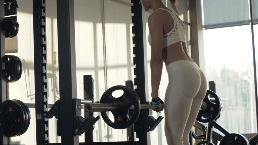 Sports woman training inclination with heavy barbell front of mirror in fitness club. Young woman making incline with fitness equipment front of mirror on gym club