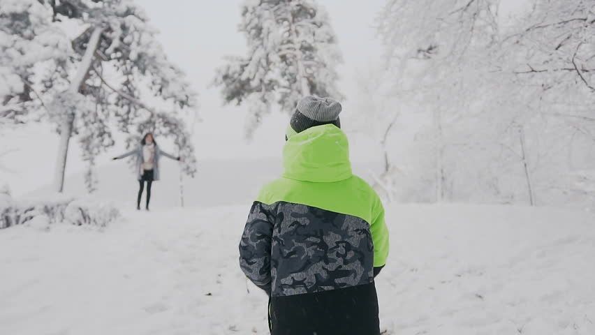 On a winter day in a snowy park, a little boy with open hands happily runs for a meeting with his mother. Happy mother and son. Christmas holidays slow motion | Shutterstock HD Video #33559834