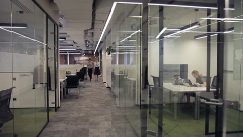 Employee works and walks around modern office with glass partitions. Two women after break are returning to their jobs in modern business center.