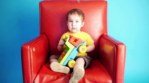 a kid playing with toy truck in red chair