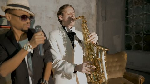 bearded man in black jacket sunglasses sings into micro and saxophonist in white stylish suit plays near sofa in club