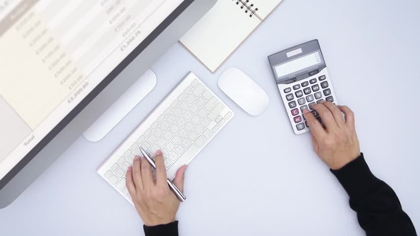 Cinemagraph of two hands pushing buttons of computer keyboard and calculator in business and financial information analysis isolated on white desktop in top view
