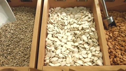 Peeled nuts and unpurified pumpkin seeds. Smooth movement of the chamber along boxes with nuts and seeds: pumpkin seed, almond, apricot seeds, cashew, hazelnuts, walnut.