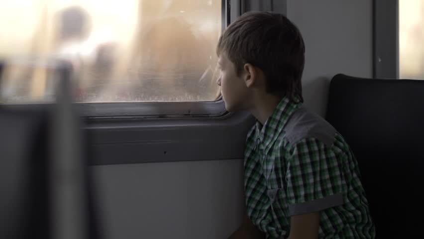 Boy is traveling by train, looking out the window | Shutterstock HD Video #33656554