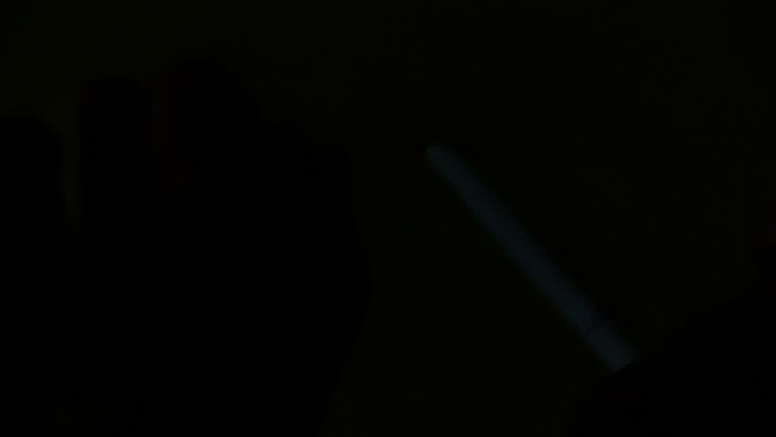 A cigarette is lit with a lighter in a completely black room. | Shutterstock HD Video #33668299