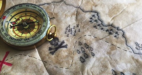 Pan camera moving over Fake pirate map with Treasure island and Nautical Compass