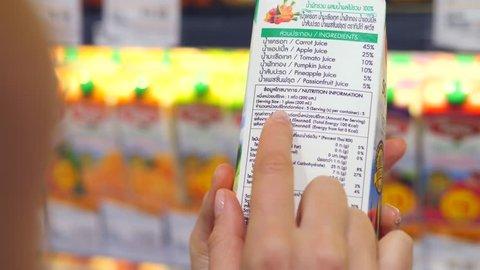 Woman Customer Reading Label On Juice Box In Supermarket. Closeup. 4K.