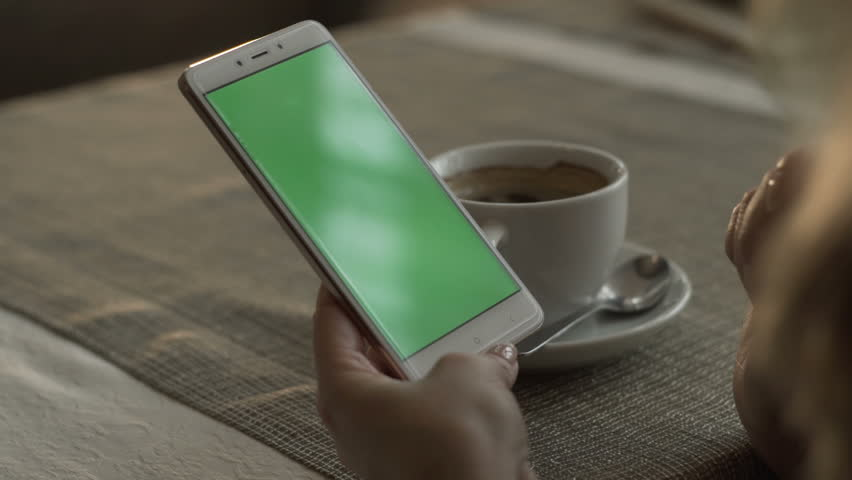 Woman hands typing on green screen mobile phone on background coffee cup on saucer standing at table in cafe. Woman using green screen smartphone. Mockup chroma key in mobile phone screen | Shutterstock HD Video #33709021