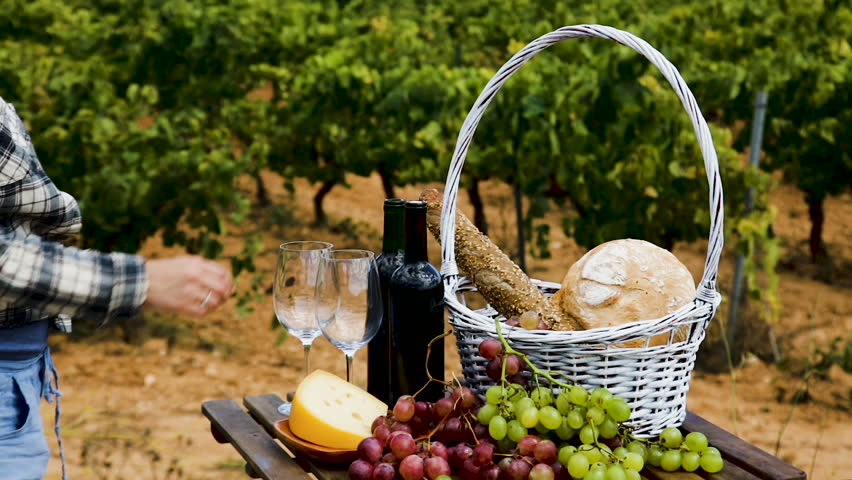 woman pouring wine into  glass. Red wine bottles and glasses on wooden table with cheese, bread and grapes overlooking vineyard