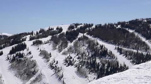 Family skis to edge of Pioneer Ridgeline to look at views of Park City Mountain, Utah with ski runs and Motherlode, Thaynes, and King Con lifts.