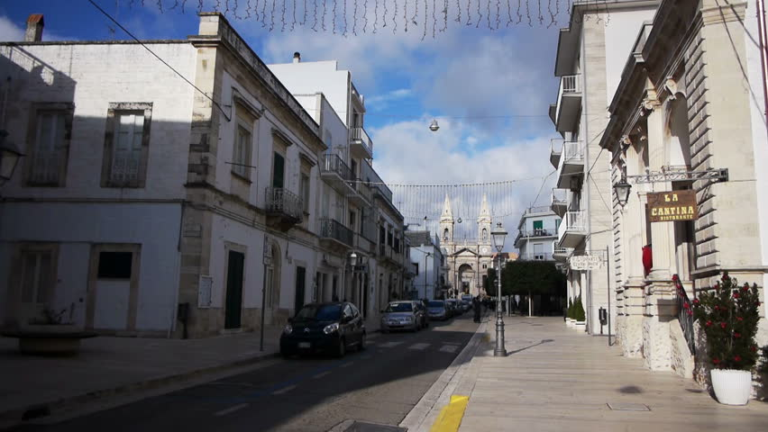 ALBEROBELLO, ITALY - December, 18: Street leading to Saint Cosma and Damiano Basilica on December, 18, 2013, Alberobello, Italy. Alberobello is UNESCO World Heritage Site highly visited all year round