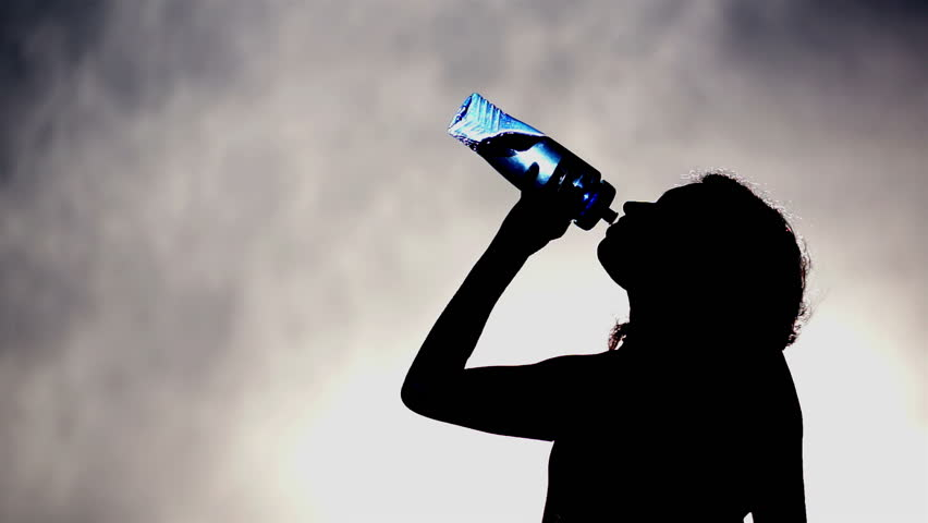 Silhouette of a woman drinking water out of a blue, translucent water bottle with a cloudy grey and blue sky background.