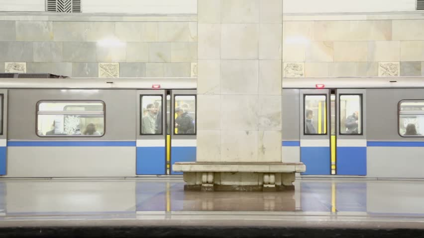 Doors close and train ride away from empty platform of metro station