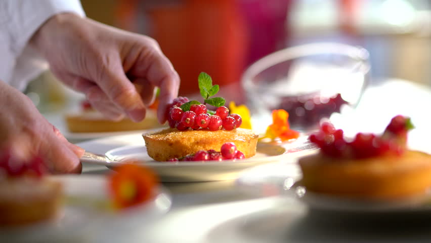 Close-up on the hands of the pastry chef decorating a cake with red currants and a mint leaf before serving.Video