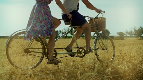 Couple man and woman riding a bicycle tandem on background summer field and haystacks. Young woman and man cycling bike tandem on rural field in summer day