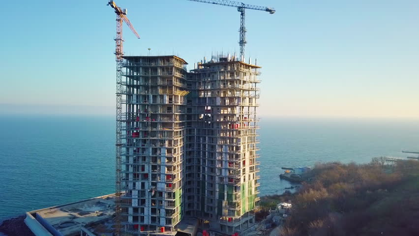 Aerial city view. Construction of a high-rise skyscraper on the ocean by two cranes. Even slow travel.