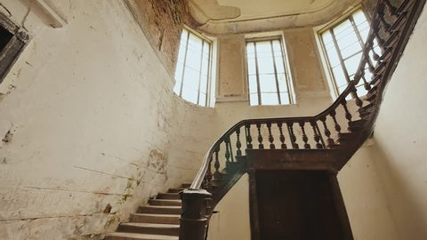 A staircase with a dark wooden railings in an abandoned architectural building. The legacy of the past.