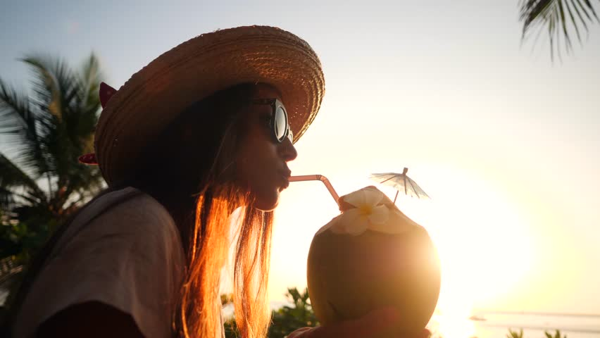 Attractive Young Tourist Hipster Girl Drinking Fresh Thai Coconut Water Cocktail at the Beach Against Beautiful Sunset. 4K, Slowmotion. Phuket, Thailand.