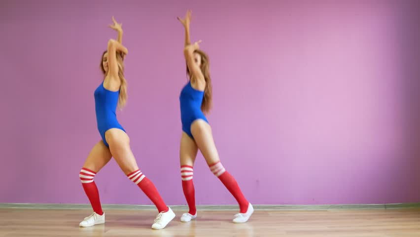 Two girls dance modern dances. Women in swimsuits and leg warmers