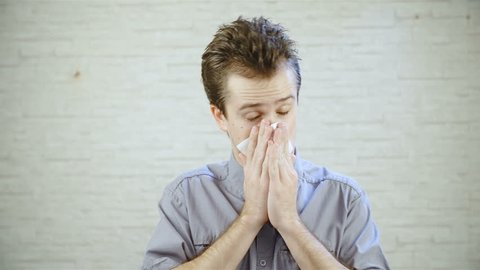 Person sneeze into a handkerchief in slow motion 4K. Static portrait shot of young man in focus looking at the camera sneezing and cleaning nose with a white handkerchief. Bright brick wall background