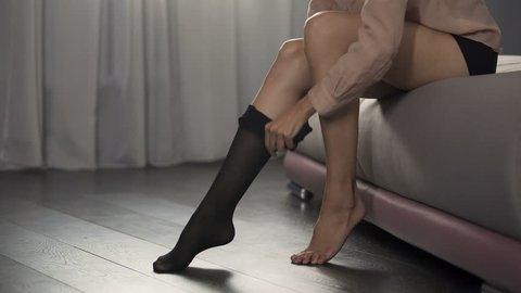 Beautiful lady slowly dressing black nylon stockings on her sexy slim legs