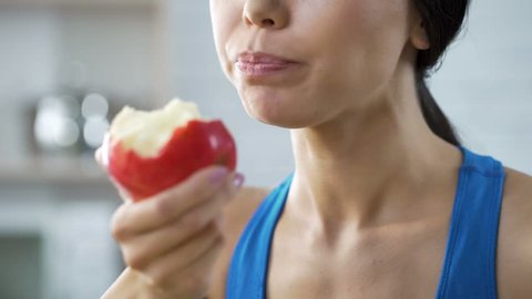 Girl eating apple replenishing her body with vitamins after grueling workout