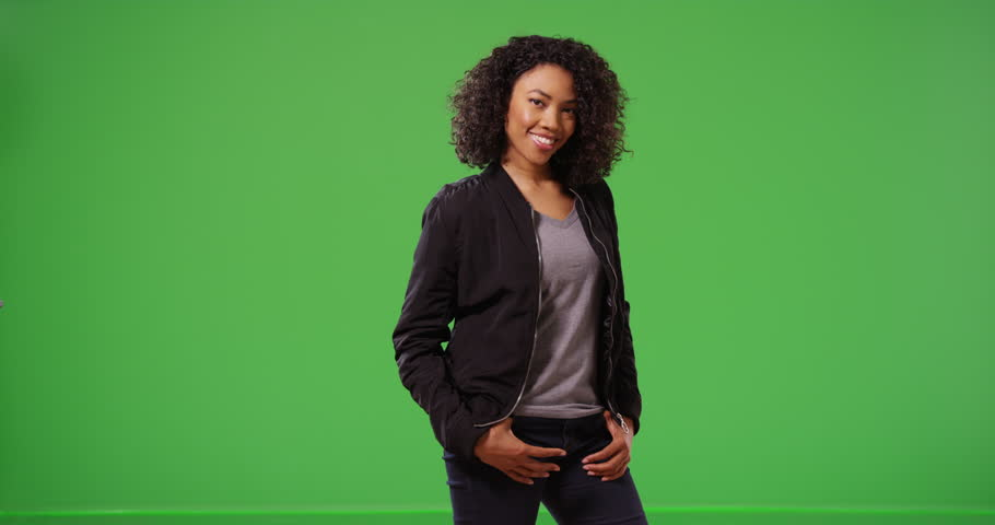 Happy woman in stylish black bomber jacket and jeans smiling on green screen. Portrait of cool African American millennial in casual clothes looking at camera on greenscreen for compositing. 4k | Shutterstock HD Video #33810454