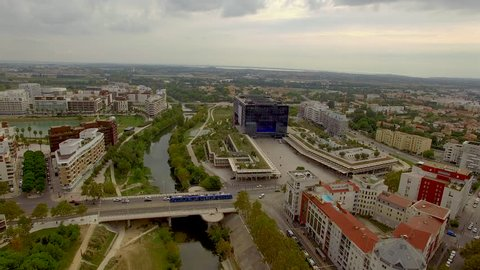 Slow aerial shot circling above the River Lez in urban Montpellier