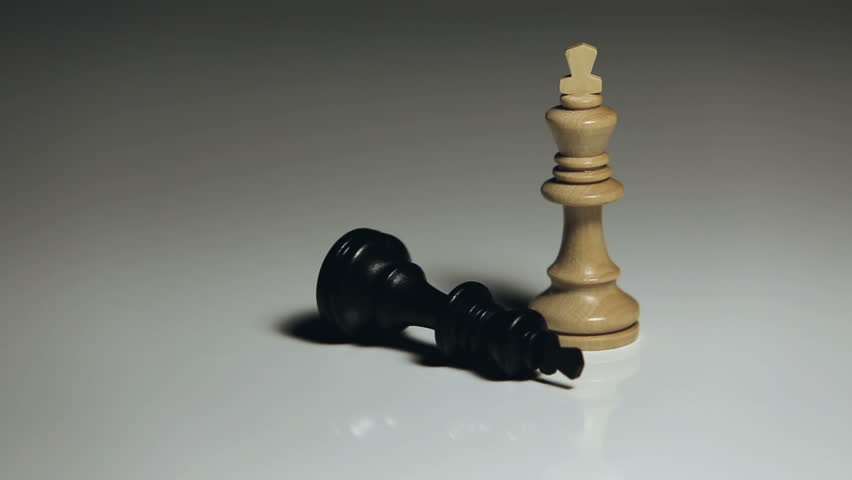 Chess pieces: a hand puts down the black king, while the white king remains standing.  | Shutterstock HD Video #33825394