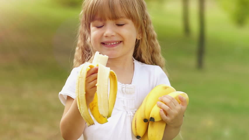 Sunny girl with bananas. The child looks at the camera. Happily eating fruit