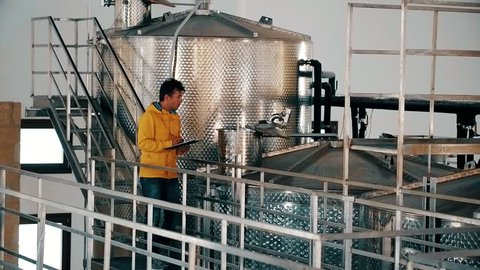 Employee sanitary epidemiological station controlling production alcohol products at factory. Worker controlling quality production wine at winery