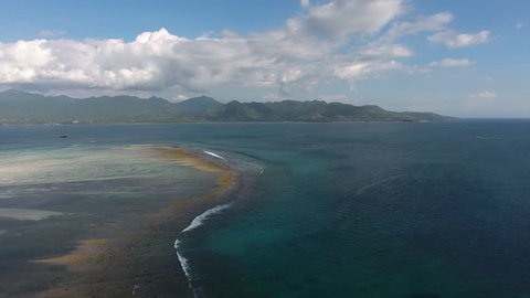 Aerial view of blue water of ocean with coral reef bottom in natural scenery and blue sky above,bird's eye view of shallow lands near island coastline with small waves running from turquoise deepness
