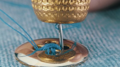 Sewing needle with a blue thread sews a button of gold color with the help of a thimble to a jeans clothes. Macro. Closeup. Shallow depth of field