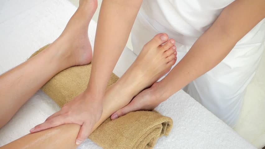 Professional therapist giving reflexology relaxing traditional Thai foot massage treatment to a woman in spa | Shutterstock HD Video #33897634