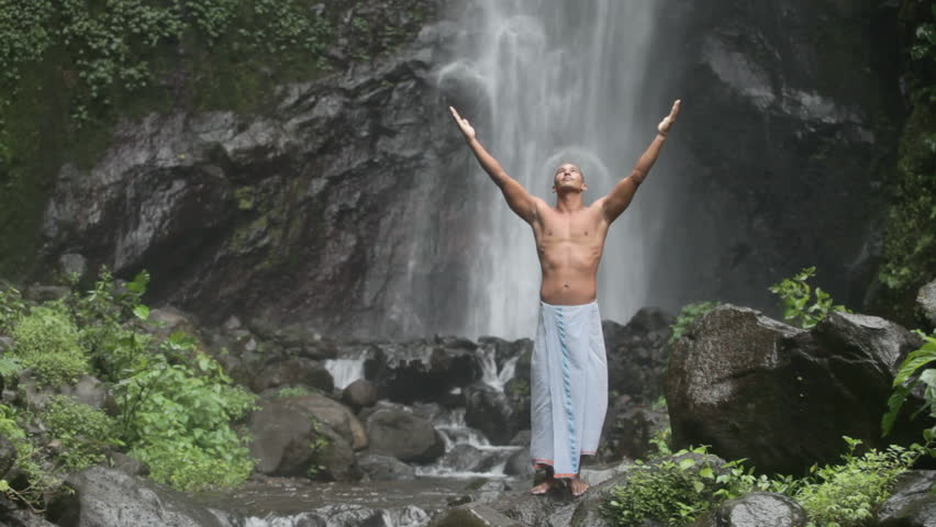 Handsome and muscular man feeling good under waterfall