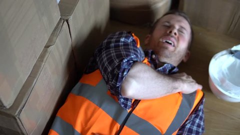 Injury at work. A male warehouse worker man is injured and in pain. For injury compensation claim. 4K.