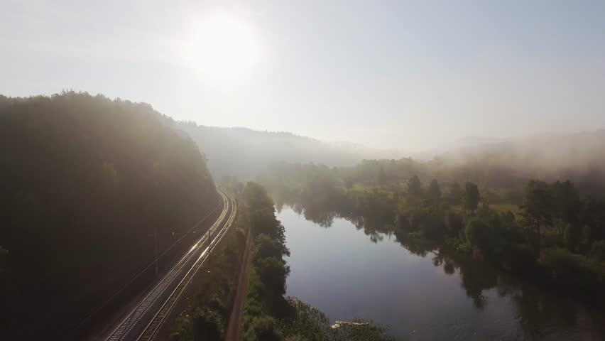 Empty winding Trans Siberian railway near the river, endless railway without train at summer foggy sunrise - aerial top view