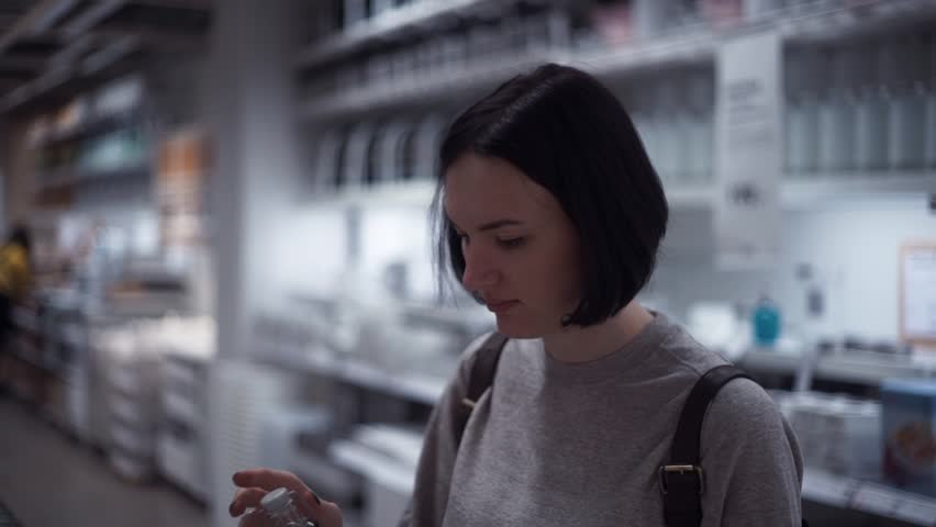 Young girl chooses glass bottle in the section of dishware in the hypermarket. Customer shopping in housewares store buying kitchen goods. Slow motion | Shutterstock HD Video #33935554